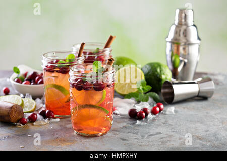 Refreshing winter cocktail with ice, lime and cranberry in mason jars - Stock Photo