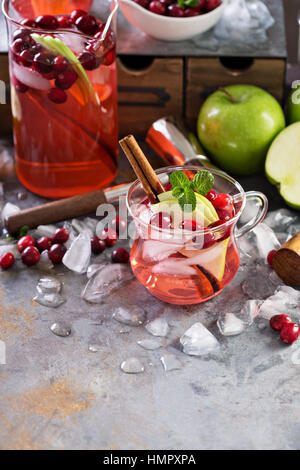 Winter refreshing cocktail with ice, apples and cranberry in glass cups - Stock Photo