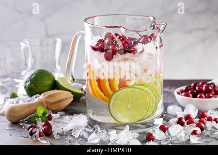 Infused water with citrus fruits and cranberry in a pitcher - Stock Photo