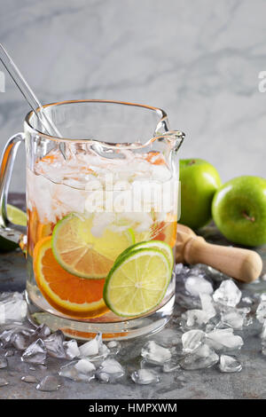 Infused water with citrus fruits in a pitcher - Stock Photo