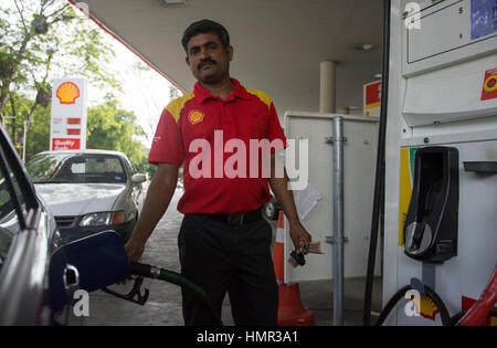an indian pump attendant is filling a car with gasoline at a shell petrol station in