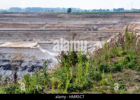 GARZWEILER, GERMANY - SEPTEMBER 01, 2016 : Sccenic view into open cast brown coal mining field with green plants - Stock Photo