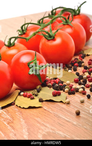 Cherry tomatoes with black pepper and bay leaf on the wooden background - Stock Photo