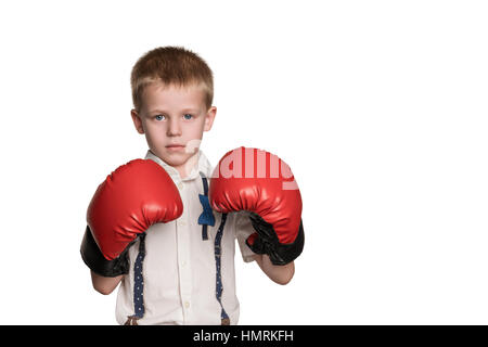 Little serious boy in shirt and red boxing gloves standing in a defensive stance isolated on white background - Stock Photo