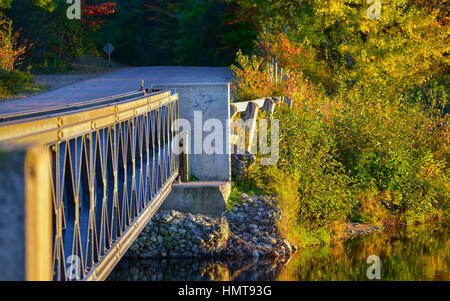 Lost love - An arrow through a blue heart valentine, painted onto a bridge abutment, golden summertime sun shines - Stock Photo