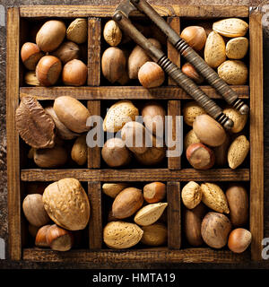 Various nuts in shell in a wooden box - Stock Photo