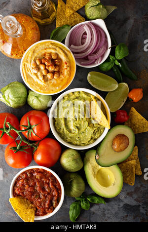 Homemade hummus, salsa and guacamole with corn chips and vegetables overhead view - Stock Photo