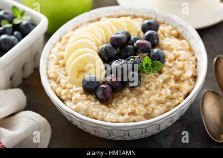 Steel cut oatmeal porridge with banana and blueberry for breakfast - Stock Photo