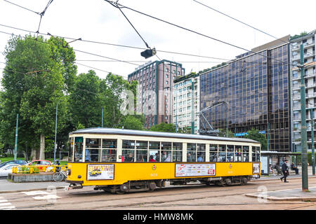 MILAN, ITALY - JUNE 14, 2016: Old vintage yellow tram with passengers on the streets of Milan city. The ATM Class - Stock Photo