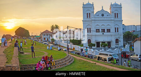 GALLE, SRI LANKA - DECEMBER 3, 2016: People walk along the fortress walls and enjoy the main town landmarks on sunset, - Stock Photo