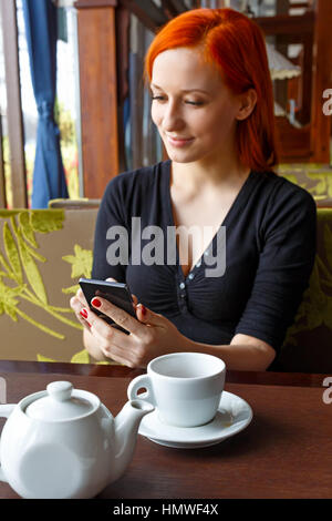 Portrait of beautiful girl in hat using her mobile phone in cafe. Tonned. Selective focus. - Stock Photo