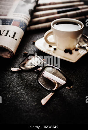 Glasses and newspaper and cup of coffee on black stone background - Stock Photo