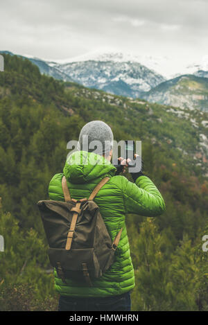 Young man traveller wearing green jacket making photo of slopes and mountains with snowy peaks in Dim Cay district - Stock Photo