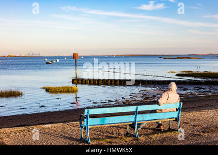 A elderly man sits on the waterfront at Gillingham Strand and looks down the river Medway in the winter morning - Stock Photo