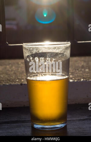 A pint of Batemans Gold beer with sunlight shining through it - Stock Photo
