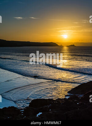 Sunset over surfers at Fistral Beach, Newquay, Cornwall, UK - Stock Photo