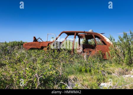 Landscape view of burnt out car amongst heathland vegetation, Feuilla Plateau, Aude, France in June 2016. - Stock Photo