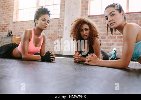 Portrait of three young women lying on gym floor and looking at camera. Females in fitness class. - Stock Photo