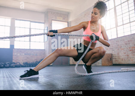 Shot of young african woman doing exercises with rope at a gym. Fitness female pulling rope at gym. - Stock Photo
