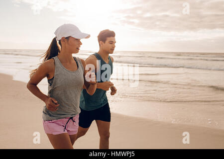 Young couple running together on the beach. Outdoor shot of young couple on morning run. - Stock Photo