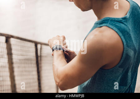 Close up shot of young man outdoors using a smartwatch to monitor his progress. Male runner resting and checking - Stock Photo