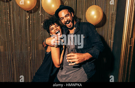 Image of happy young couple having fun at disco. Young man and woman enjoying a party. - Stock Photo