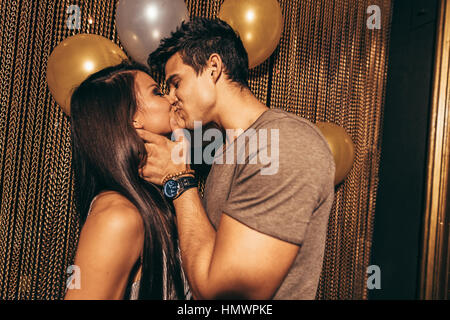 Shot of romantic young couple kissing in the night club. Man and woman in the pub. - Stock Photo