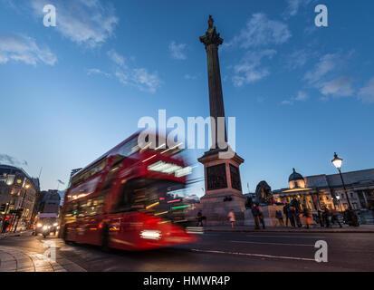 Red London bus travelling past Trafalgar Square - Stock Photo