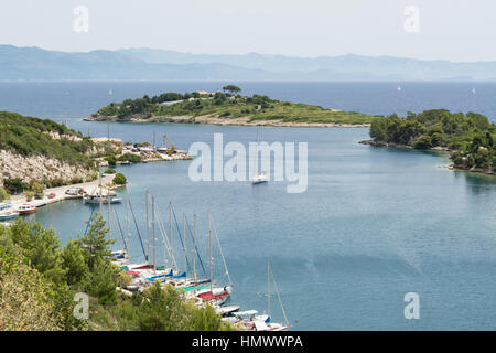 The small island of Panayia at the mouth of Gaios harbour, Paxos, Greece, with the Greek mainland in the distance - Stock Photo
