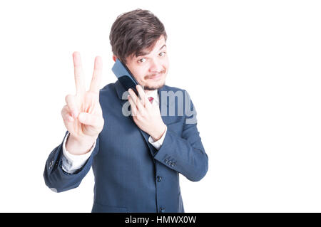 Marketing manager talking at phone showing peace sign or gesture isolated on white background with copy advertising - Stock Photo