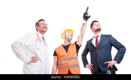 Low angle shot of group of people with different professional occupations indicate something on white background - Stock Photo