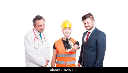 Joyful builder pointing on virtual screen while standing near medic and businessman on white background - Stock Photo