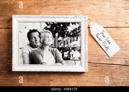 Photo of seniors in picture frame laid on wooden background. - Stock Photo