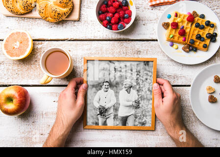 Hands holding picture of seniors, breakfest meal. Studio shot. - Stock Photo