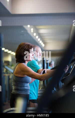 Beautiful fit senior couple in gym doing cardio work out. - Stock Photo