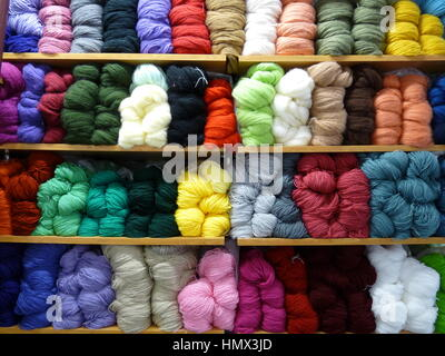 Shelves full of rows of brightly-coloured skeins of yarn or balls of wool in a variety of colours in a craft shop - Stock Photo