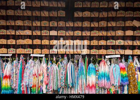 Small wooden plaques with prayers and wishes & colourful paper cranes at Fushimi Inari Taisha (Shinto shrine), Kyoto, - Stock Photo