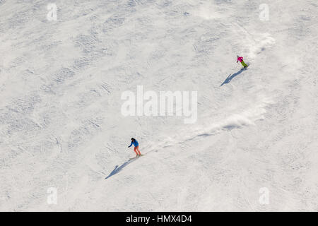 Two skiers on a steep black ski run with trails of snow dust behind them. - Stock Photo