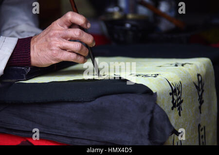 Close up of old man's hand writing ancient chinese characters on a scroll at a in Hanoi, Vietnam, South East Asia. - Stock Photo