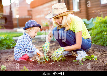 Child and mother planting strawberry seedling into fertile soil outside in garden