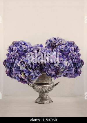 Still life with purple artificial Hydrangeas and silver plated brass antique ice bucket. - Stock Photo