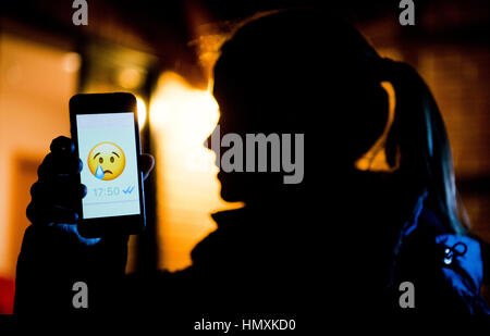 Hanover, Germany. 4th Feb, 2017. ILLUSTRATION - A young girl shows the display of a smartphone with a crying emoji - Stock Photo