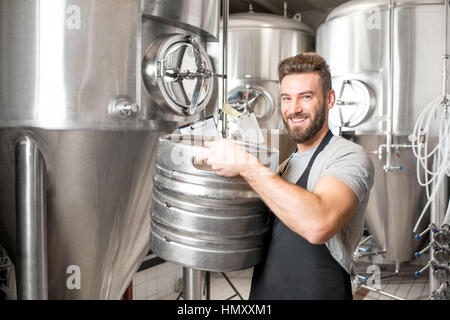 Worker carrying barrel with beer at the brewery with metal containers on the background - Stock Photo