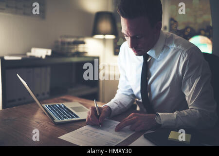Businessman working concentrated on documents at night, working overtime at office - Stock Photo