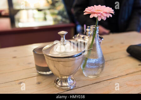 ESSEN, GERMANY - JANUARY 25, 2017: Table decoration with rose coloured flower in a cafe - Stock Photo