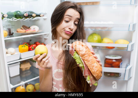 Young woman choosing between apple and big sandwich standing in front of the refrigerator full of vegetables and - Stock Photo