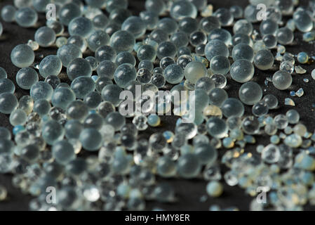 macro of silica gel balls laying on black background - Stock Photo