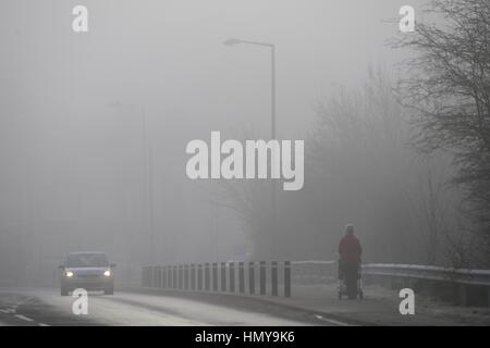 A woman pushes a child in a buggy in the fog at Barnsley, South Yorkshire. - Stock Photo