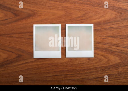 Blank instant print photographs on wooden table. Two Objects. - Stock Photo