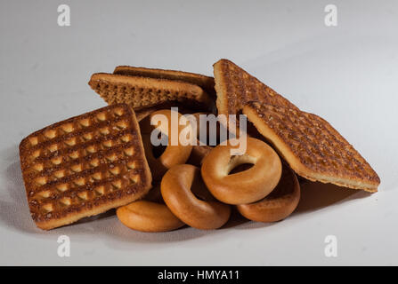 stack of square crackers with pieces and crumbs on slate gray background. - Stock Photo